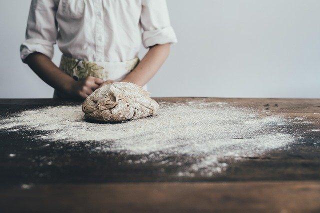 エプロンをつけてパンをこねている