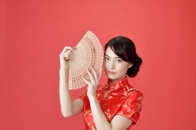 扇子をもつチャイナ服の女性