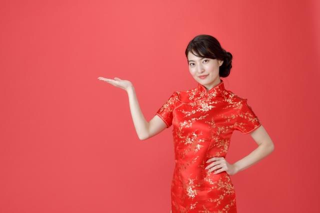 手を挙げるチャイナ服の女性